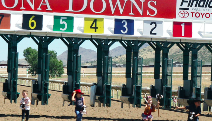 Kids on stick horses in front of a starting gate.